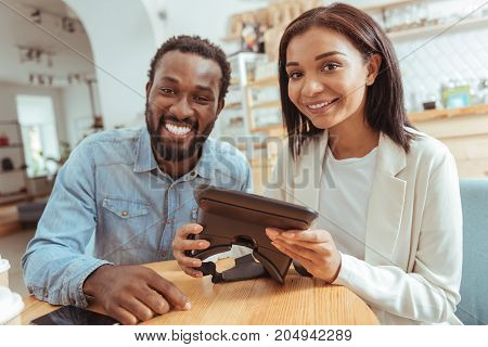 Technology lovers. Pleasant cheerful best friends sitting in the coffeehouse, holding a VR headset and smiling at the camera broadly