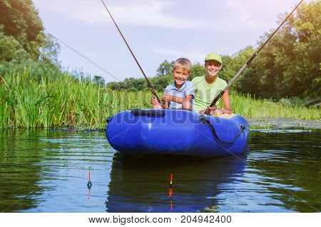 Lonely child fishing on river on the summer day