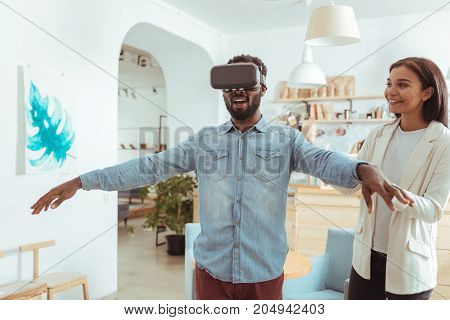 For the first time. Excited young man wearing a new VR headset and spreading his hands wide while the woman supporting him during his first virtual reality experience