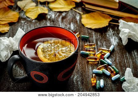 autumn cold - treatment with hot tea and medecine on wooden background