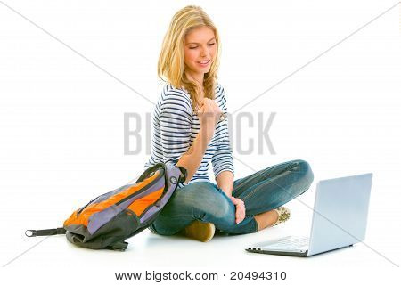 Pleased teengirl sitting on floor with schoolbag and laptop isolated on white