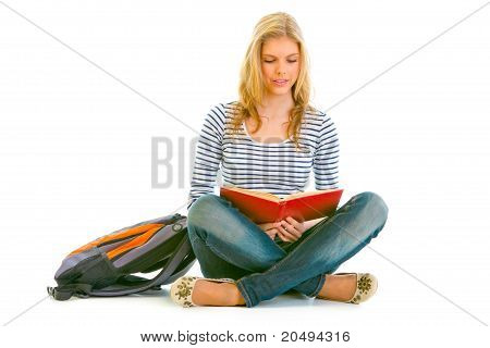 Pensive teengirl with schoolbag sitting on floor and reading book isolated on white
