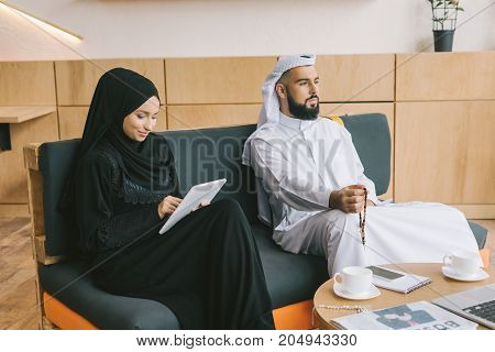musilim woman sitting on couch and using tablet while her husband looking away thougtfully