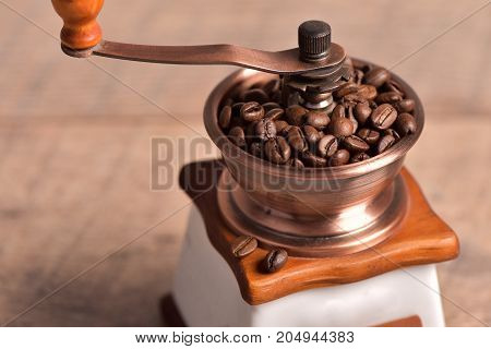 Grinding coffee beans by rotary coffee grinder. Antique coffee grinders for grinding your coffee bean for breakfast.