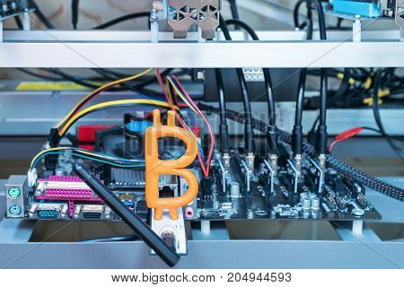 Plasticine bitcoin sitting on a modem in a computer farm for  mining cryptocurrency