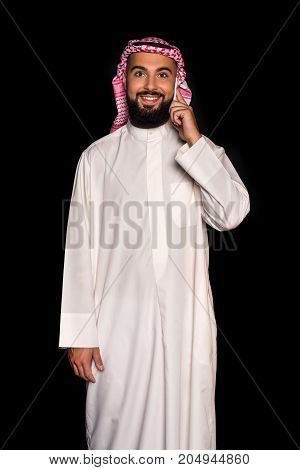 smiling muslim man talking by phone isolated on black
