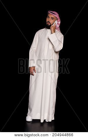 handsome muslim man talking by phone isolated on black