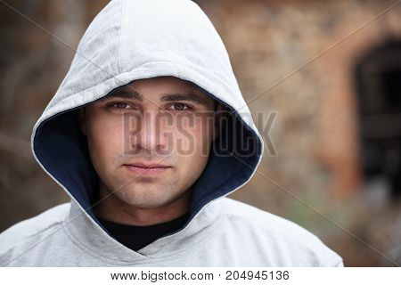 A handsome young man in a gray hood