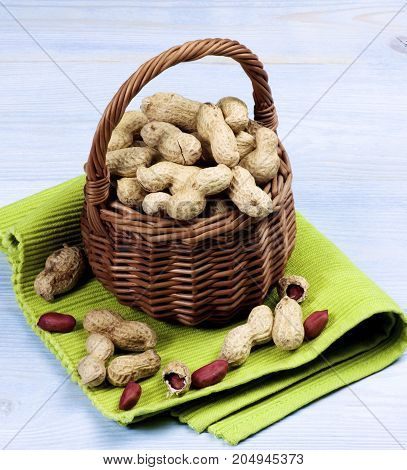 Arrangement of Fresh Peanuts with Nutshell in Wicker Basket on Green Napkin closeup on Wooden background