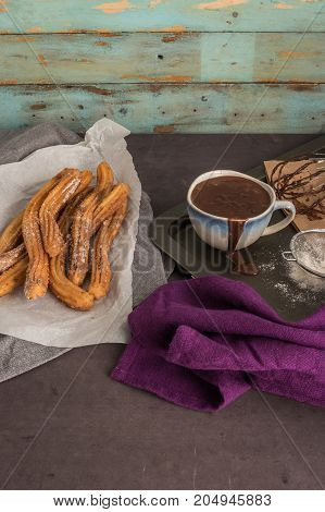 Traditional Spanish and Mexican dessert churros with hot chocolate sauce on black stone background.