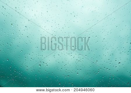 Rain drops on glass selective focus. Cloudy sky background