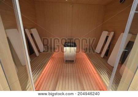SPA sauna interior of infrared heating with wooden covering and colored lighting of the floor and ceiling