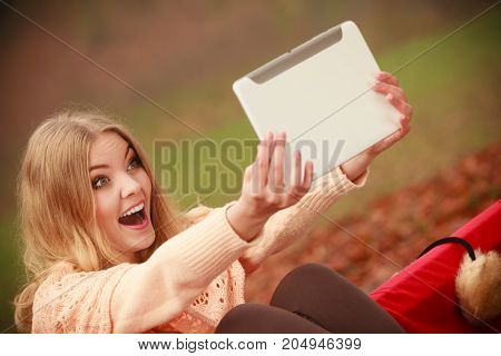 Modern education concept people outside. Girl sitting on bench with tablet. Attractive young blonde woman with digital equipment.