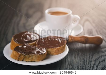 breakfast with espresso and baguette slices with chocolate spread, rustic style