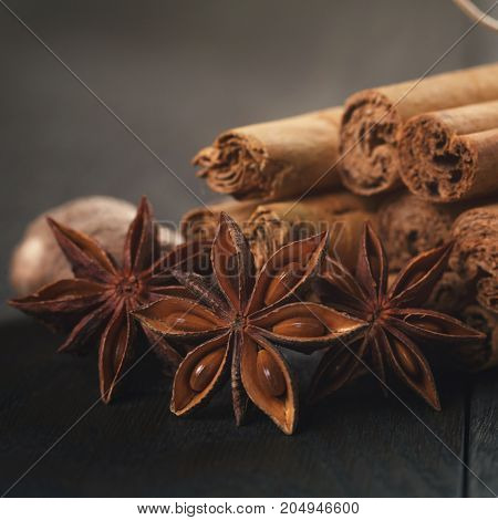 bunch of cinnamon sticks with nutmeg and anise star, on rustic oak table