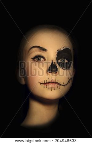 Halloween, holidays, masquerade concept - the portrait of young little beautiful girl with skull makeup on black background. Halloween, face-art, skull make up concept.