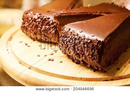 Close up pieces of delicious chocolate cake on wooden board