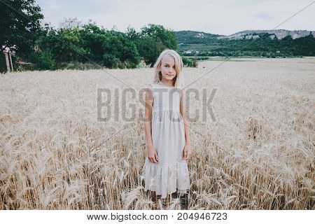 Beautiful cute girl in a wheat field in a beige dress.