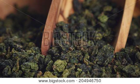 oolong green tea in wood bowl, close up