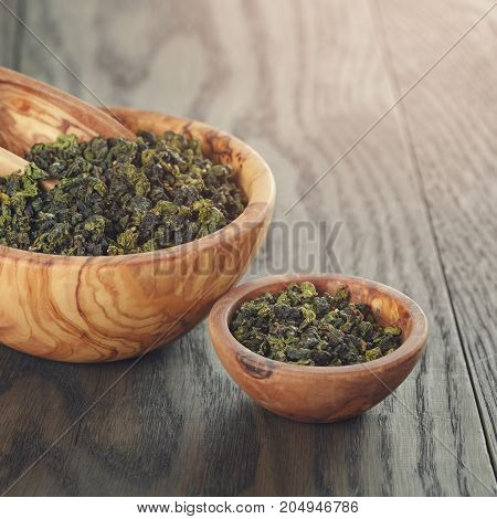 oolong green tea in olive bowl, on oak table
