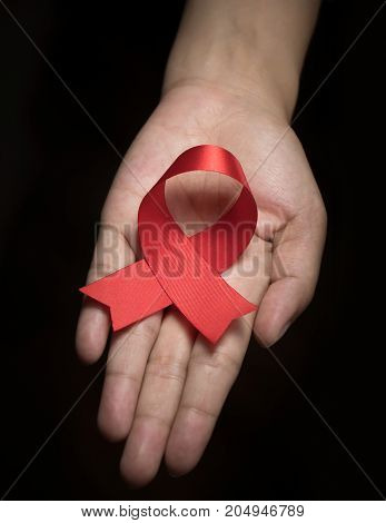 Red ribbon awareness on woman human hand : World aids day satin ribbon symbolic concept raising concerns/ help campaign on people health public support on HIV STD heart disease