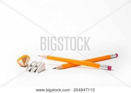 Two Pencils with pencil sharpener and sharpening shavings on white background. stationery. Office tool.