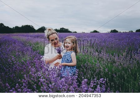 Smiling mom and daughter in a lavender field. Mother's Day concept.