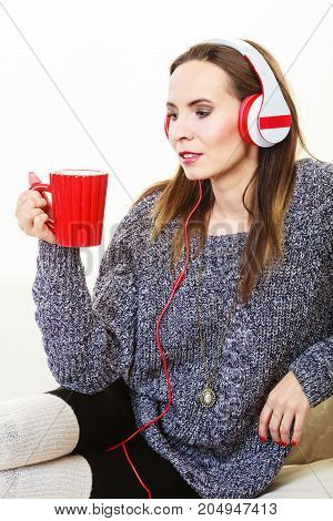 People leisure relax concept. Woman casual style red big headphones listening music mp3 sitting on couch at home relaxing drinking hot tea coffee