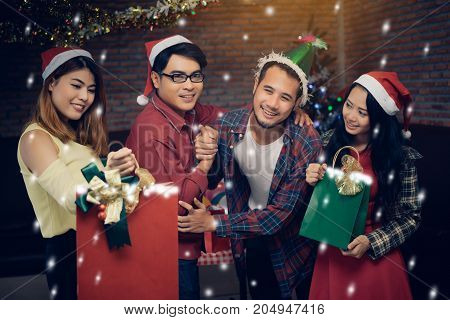 Young men and women group holding paper bag surprise christmas party together with dance drinking wine happy and fun in new year celebrate