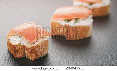 small sandwiches with soft cheese and salmon on slate background