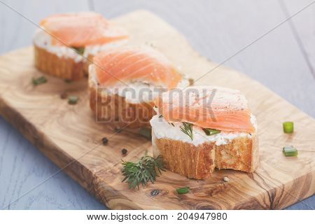 baguette slices with soft cheese and salmon on wood table, vintage toned