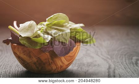 green and purple basil leaves in wood bowl on wooden table, copy space for text