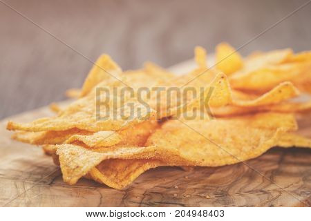 heap of tortilla chips on olive board on wooden table, selective focus