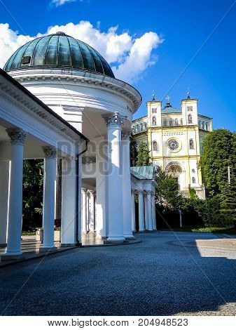 The colonnade with mineral water sources on Church of the Assumption of the Virgin Mary background in Marianske Lazne (Marienbad) Czech Republic