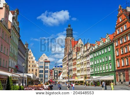 Wroclaw/Poland- August 17, 2017: cityscape of old town Market Square with colorful historical buildings, shops and restaurants, citizens ant tourists walking around