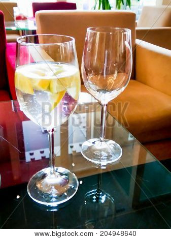 Glass of lemonade and slices of lemon cooked in a bar on a glass table
