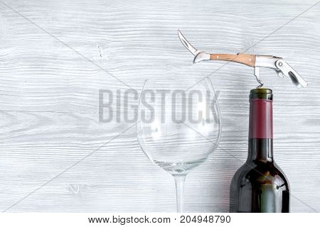 glass wine bottle and corkscrew on wooden background top view.