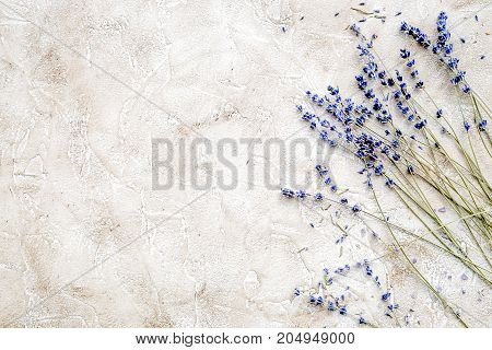 Essential oil and lavender salt with flowers top view gray background