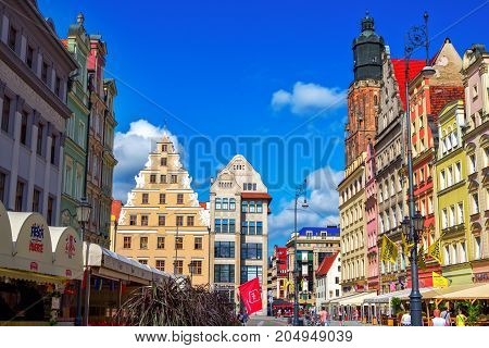 Wroclaw/Poland- August 17, 2017: cityscape of old town Market Square with colorful historical buildings, open air restaurant sunshades and blue sky