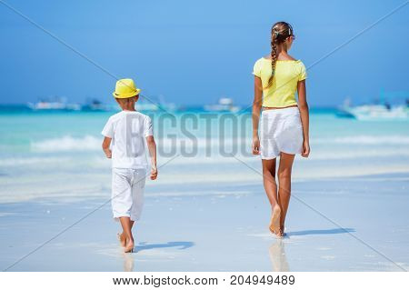 Little boy wearing white with his sister walking on tropical ocean beach. Kid during family sea vacation. Summer water fun.