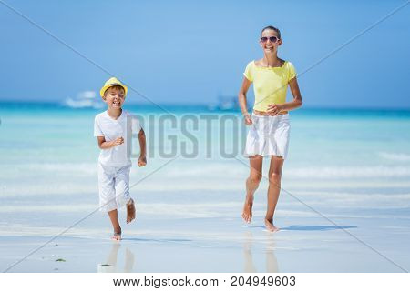 Little boy wearing white with his sister having fun on tropical ocean beach. Kid during family sea vacation. Summer water fun.