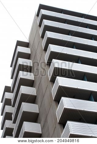 large modern apartment block with external balconies in horizontal pattern with concrete walls and white sky