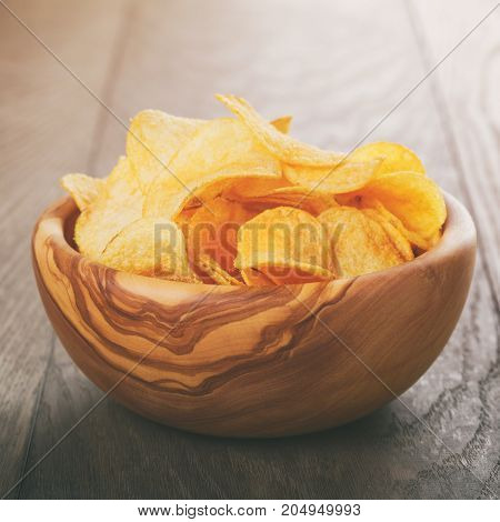 potato chips with paprika, on wood oak table