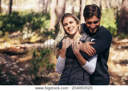 Man Holding His Woman Partner From Behind In Forest