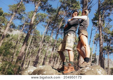 Woman Holding Her Male Partner From Behind Standing On Rocks