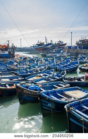 Many blue wooden fishing boats anchored in historic port of medieval town Essaouira, Morocco, North Africa.