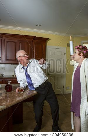 Drunk Man With Wife In Kitchen With Rolling Pin