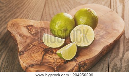 ripe limes on olive board, rustic style