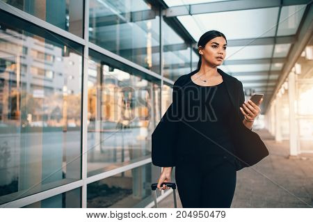 Beautiful young businesswoman walking outside public transportation station. Caucasian female traveler with suitcase at airport.