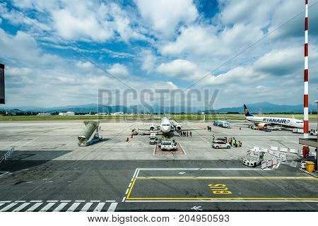 Milano Italy - MAY 10 2017: Resupplying and servicing Ryanair plane for flight from Milano Italy to Santiago de Compostela Spain on a sunny day. Terminal with Ryanair planes. Ryanair is biggest budget low-cost airline in the world.